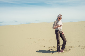 Woman is standing in the desert and is looking at a smartphone