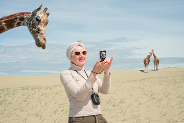 Woman is standing next to a giraffe and photographs