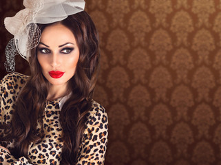 Beautiful retro brunette woman portrait in leopard blouse with red plump lips in vintage veil hat on brown pattern blur background with copy space