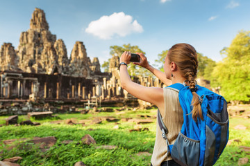 Young female tourist taking picture of Bayon temple in Angkor