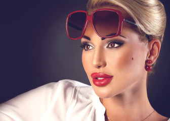 Portrait of beautiful blonde woman in sunglasses and red plump lips on dark background with copyspace