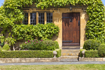Brown wooden doors to traditional English stoned cottage, garden