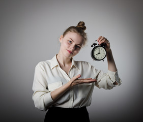 Girl pointing at a clock.