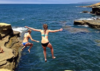 Two Young Daring Women jumping off cliff into ocean, San Diego, CA