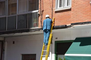 electricista trabajando sobre una escalera