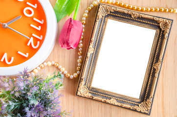 Vintage blank photo frame and clock with flower on wooden backgr