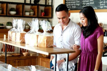 happy young couple dating at bakery shop