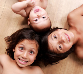 three little brothers smiling while lying on the floor