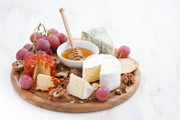 cheeses and snacks on a board on white wooden table