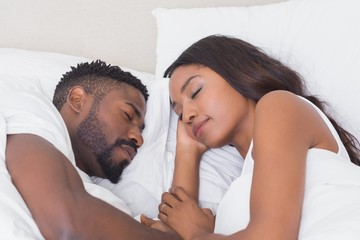Happy couple sleeping in bed together