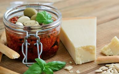 Parmesan - Zutaten für Tomatenpesto / Einmachglas auf Holztisch, Basilikum, Pinienkerne