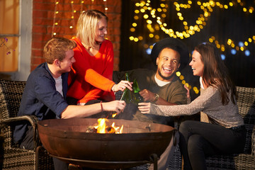 Group Of Friends Enjoying Evening Drinks By Firepit