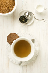cup of tea with milk  sugar and cookie