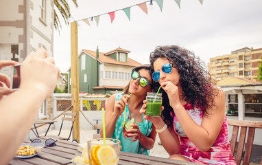 Young women couple drinking healthy drinks outdoors