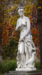 Mythological old classical statue with autumnal leaves in public park
