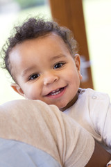 Close up shot of a baby boy being carried, smiling at the camera.