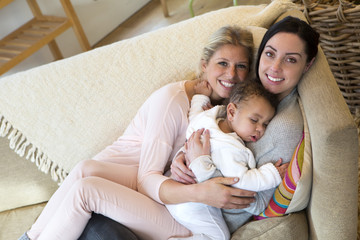 Same sex female couple cuddling on the sofa with their sleeping son