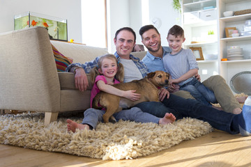 Same sex male couple sitting on the floor in their living room with their son and daughter. Their pet dog is lying across them.
