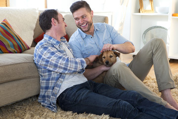 Same sex male couple sitting on the floor in their living room with their dog.