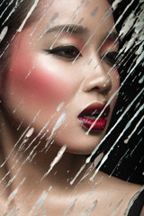 Beautiful Asian girl with bright make-up behind glass and drops