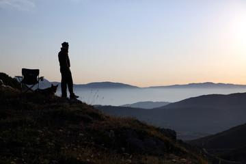 uomo guarda l' alba sulle montagne e nebbia