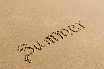 Summer - text written by hand on sand on a beach