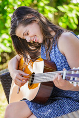 Portrait of very cute teenager playing guitar in her garden