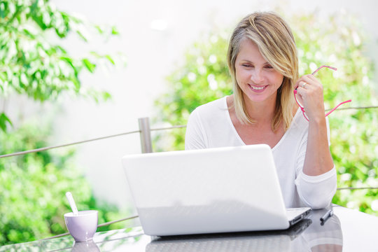 smiling woman working on a computer at home with green garden on her background