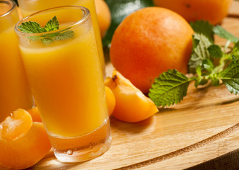 Fresh apricot juice and apricots with mint on wooden board, sele