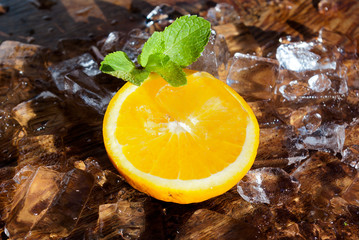 Orange slice with mint leaf on top of ice cubes