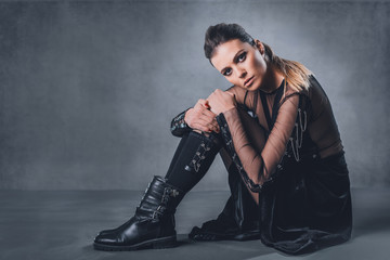 Fashion portrait of a young woman sitting in a leather dress and shoes. Studio shot.