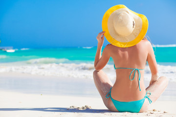 back view of a woman in bikini and straw hat at a tropical