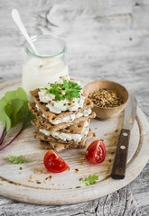 rye biscuit with cheese, cucumber and cilantro on a light wooden background - healthy snack