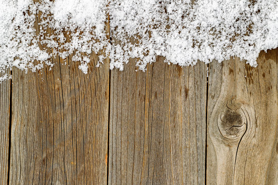Christmas border decoration with snow on rustic wooden boards