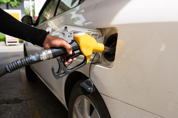 Hand refilling the car with fuel, focus hand