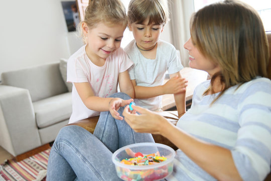 Kids getting candies from their mom