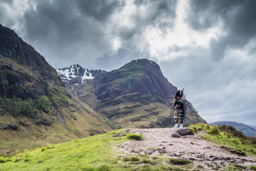 Traditional scottish bagpiper in full dress code in the highlands