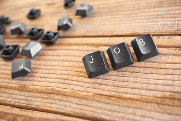 """JOB"" wrote with keyboard keys on wooden background"