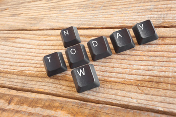 """TODAY NOW"" wrote with keyboard keys on wooden background"