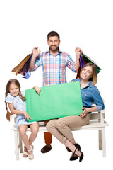 Happy family with shopping bags sitting at studio