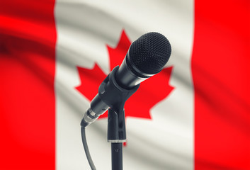 Microphone on stand with national flag on background - Canada