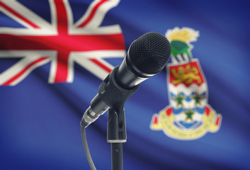 Microphone on stand with national flag on background - Cayman Islands
