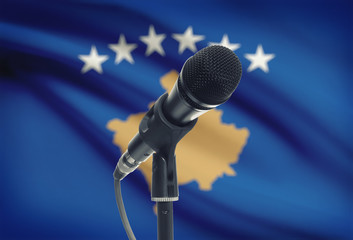 Microphone on stand with national flag on background - Kosovo