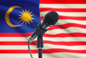 Microphone on stand with national flag on background - Malaysia