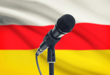 Microphone on stand with national flag on background - South Ossetia