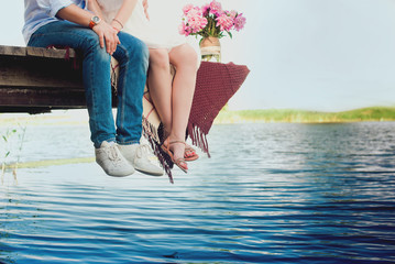 Pretty strong young loving couple sitting on the bridge over the river, next to a bouquet of peonies, lifestyle, concept, love, tenderness