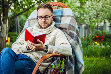 Young friendly man with red book in a summer garden at sunset.
