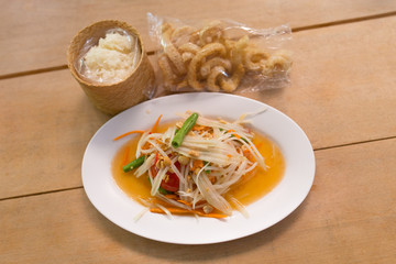 papaya salad in dish with sticky rice and  Pork rind