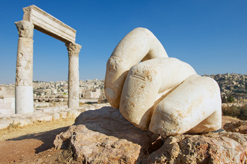 Stone Hercules hand at the antique Citadel in Amman, Jordan. At the background: ruins of the Hercules temple and Amman city.