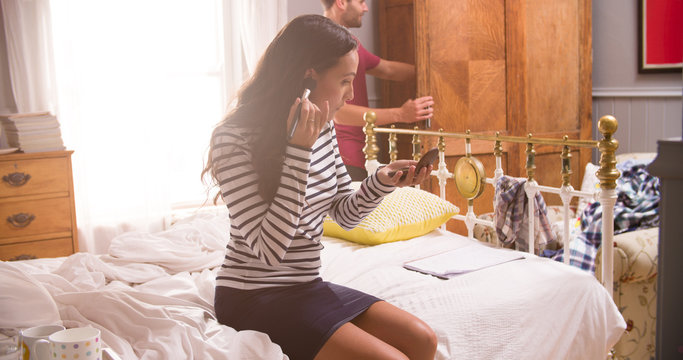 Woman Putting On Make Up And Man Getting Dressed In Bedroom